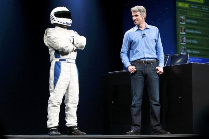 Craig Federighi, Apple Senior Vice President, Software Engineering stands on stage with a man in a racing suit, AKA, Fake Stig, to demo Racer OS X during the Apple Worldwide Developers Conference 2012 in San Francisco