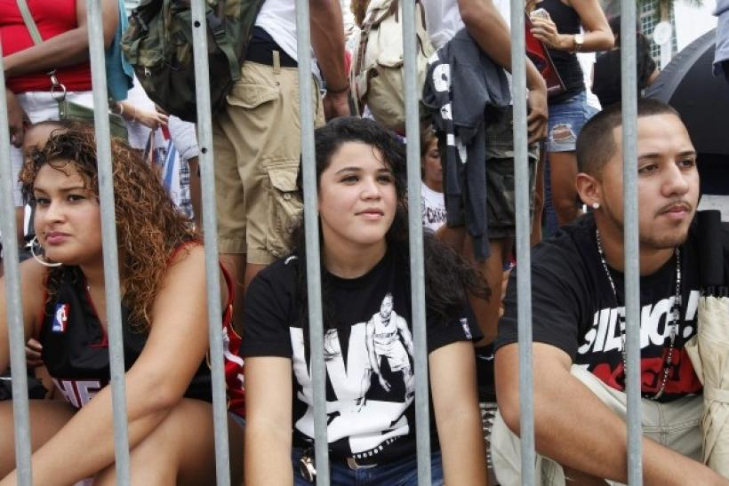 Fans await the caravan of Miami Heat players and personnel behind a pedestrian barricade along the parade route in Miami