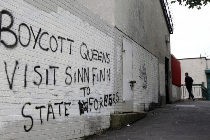 A man walks past graffitti painted on a wall in a nationalist area of north Belfast during Britain's Queen Elizabeth's two day tour of Northern Ireland