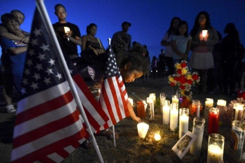 A young boy places a candle by an American flag during a vigil for victims behind a theater where a gunman open fire in Aurora, Colorado