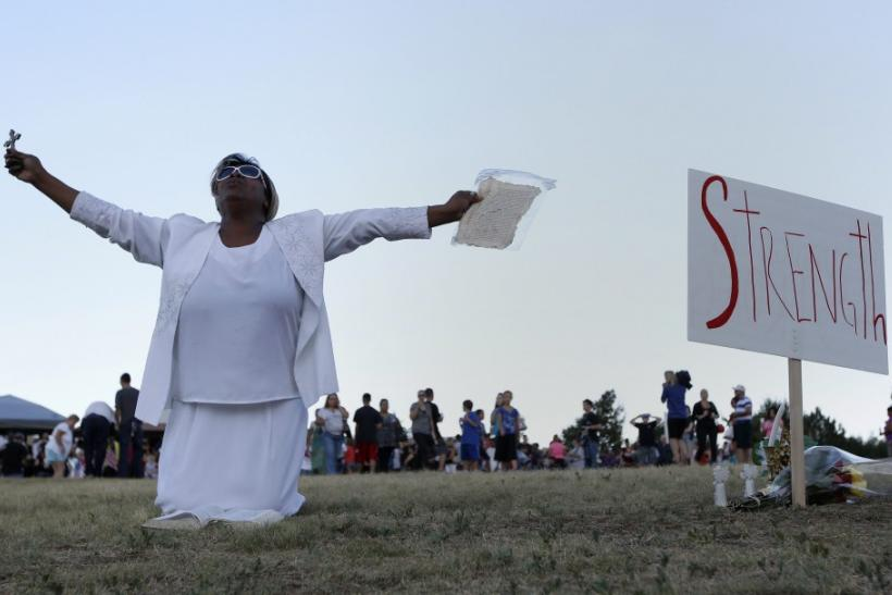 Marietta Perkins prays during a vigil for victims behind the theater where a gunman opened fire in Aurora, Colorado