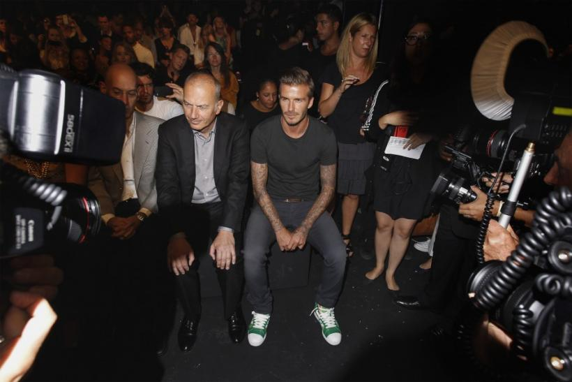 Soccer star David Beckham (R) sits with Adidas executive Erich Stamminger (C) before a presentation of the Y-3 Spring/Summer 2013 collection during a walk through at New York Fashion Week September 9, 2012.