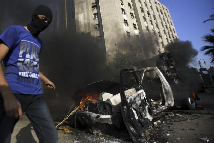 A protester walks after he set fire to a police vehicle during clashes with riot police along a road which leads to the U.S. embassy, in Cairo
