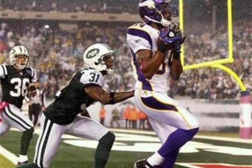 Minnesota Vikings' wide receiver Randy Moss catches a touchdown pass from quarterback Brett Favre in the second half of their NFL football game against the New York Jets in East Rutherford, New Jersey, October 11, 2010.
