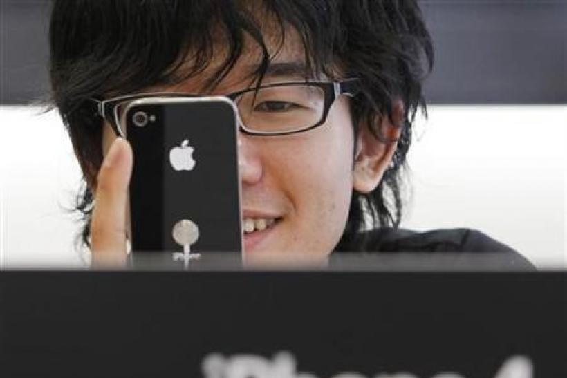 A customer tries out the iPhone 4 at Apple Inc's store in the Ginza district of Tokyo
