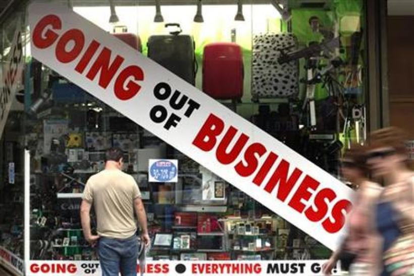A man stands outside a store advertising that it is going out of business in New York