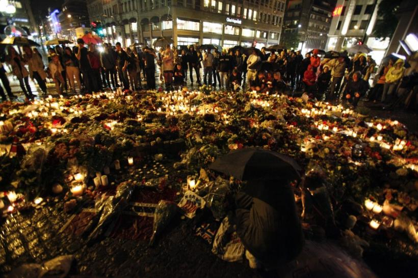 People stand under umbrellas during heavy rain as they mourn for the for the victims of a bomb blast in the capital and a rampage on nearby Utoeya island, in front of a sea of candles and flowers, in Oslo
