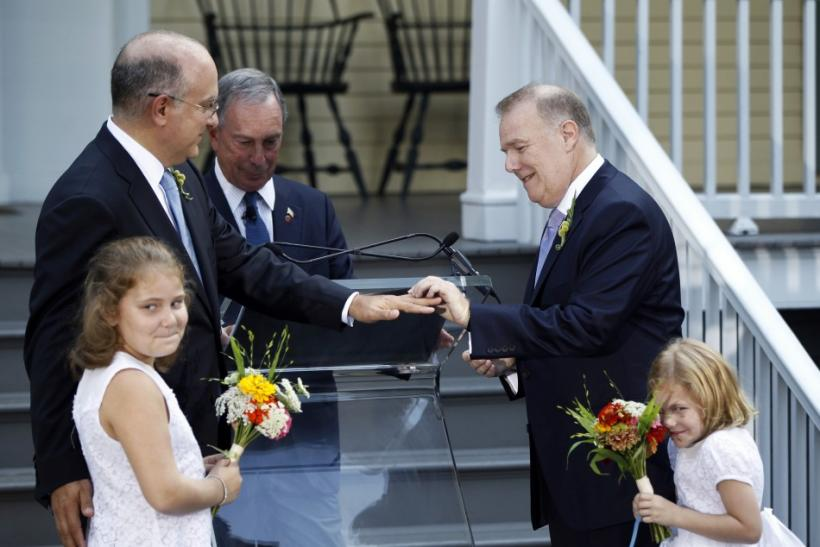 Jonathan Mintz (2nd L), New York City's consumer affairs commissioner, has a wedding ring placed on his finger by John Feinblatt (R), a chief adviser to the mayor, as they stand with daughters Maeve (L) and Georgia during a marriage ceremony presided by N