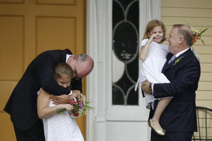 Jonathan Mintz (L), New York City's consumer affairs commissioner, and John Feinblatt (R), a chief adviser to the mayor, embrace their daughters Maeve (2nd L) and Georgia after being married by New York City Mayor Michael Bloomberg at Gracie Mansion in Ne
