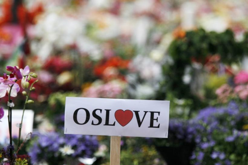 A sign of love for Oslo is seen inside of a sea of flowers and lit candles placed in memory of those killed in Friday's bomb and shooting attack in front of Oslo Cathedral
