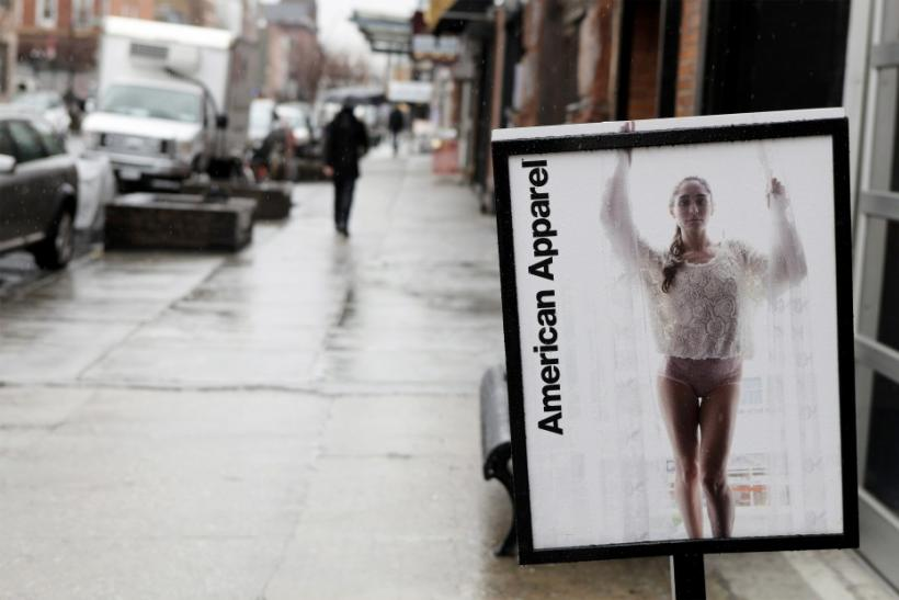 Pedestrians walk past an American Apparel sign outside one of their stores in New York