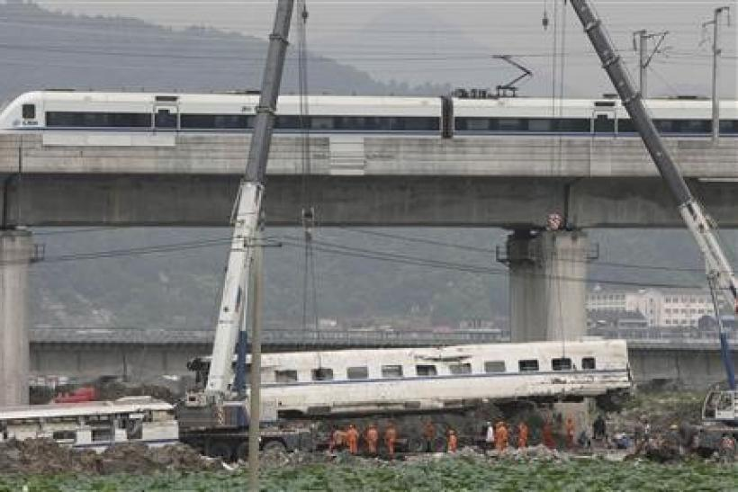 A high speed bullet train runs past a railway bridge as workers use cranes to lift a wrecked carriage