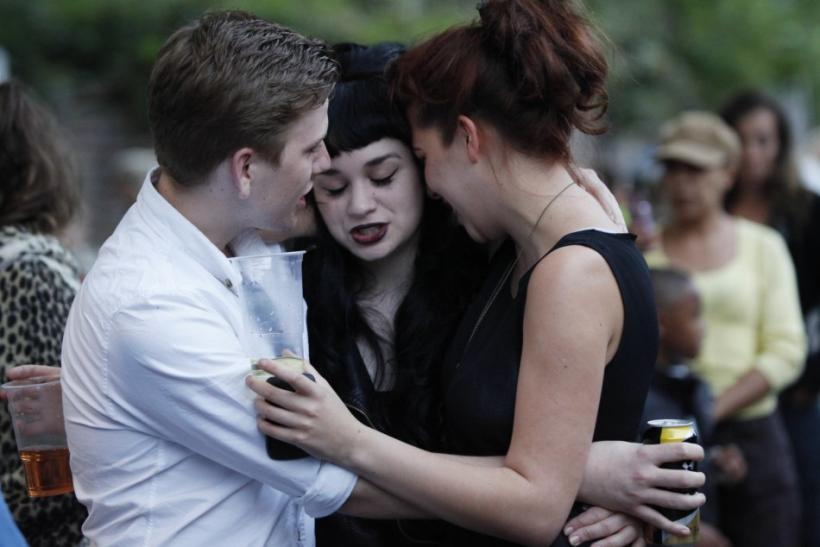 Fans embrace outside the house of British singer Amy Winehouse, following her funeral earlier in the day, in north London