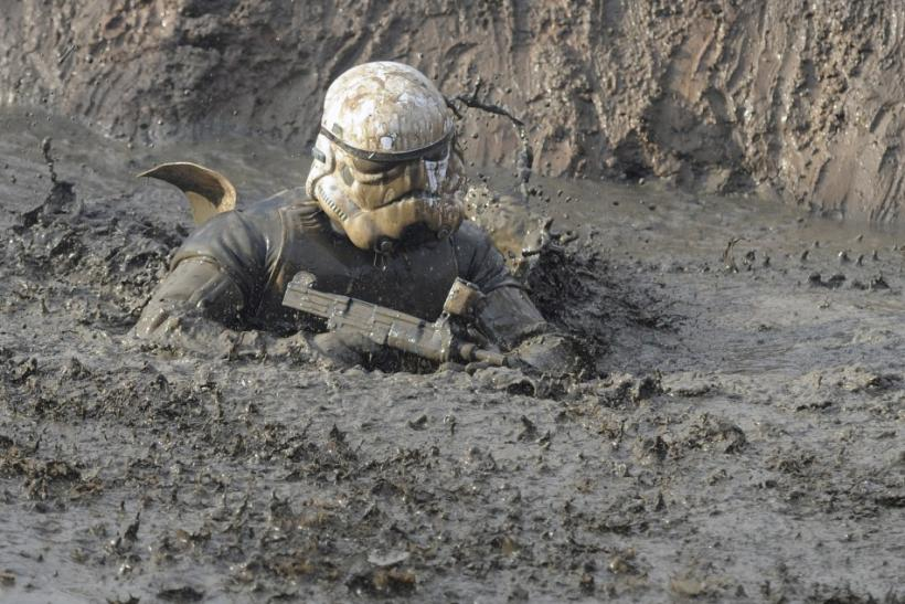 "Competitor wearing a ""stormtrooper"" helmet wades through water during the Tough Guy event in Perton"