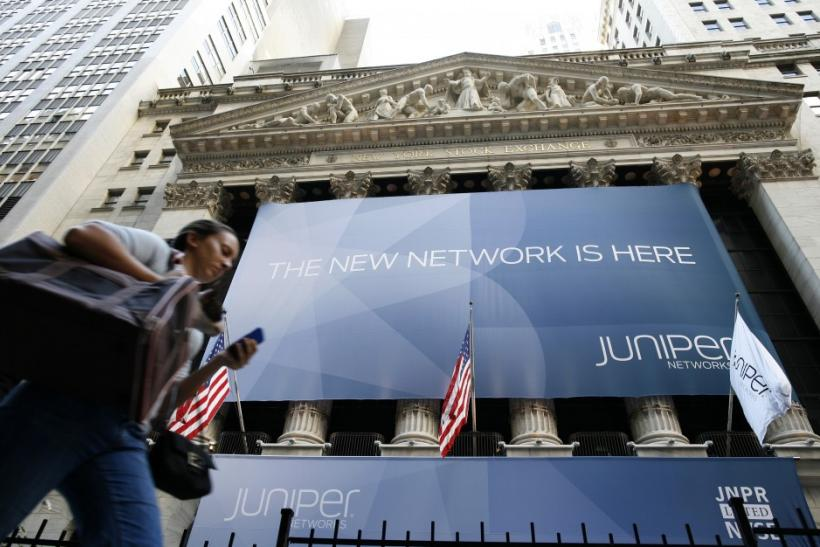 A woman walks past a banner with the logo of Juniper Networks Inc. covering the facade of the New York Stock Exchange 29/10/2009