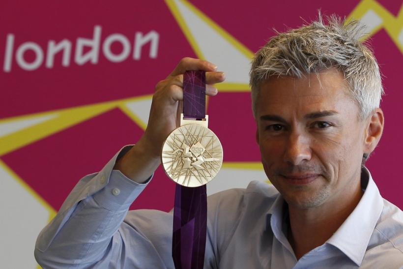 Britain's Olympic triple jump gold medalist Jonathan Edwards, poses for a photograph with a gold medal designed for the London 2012 Olympic Games following a news conference in London