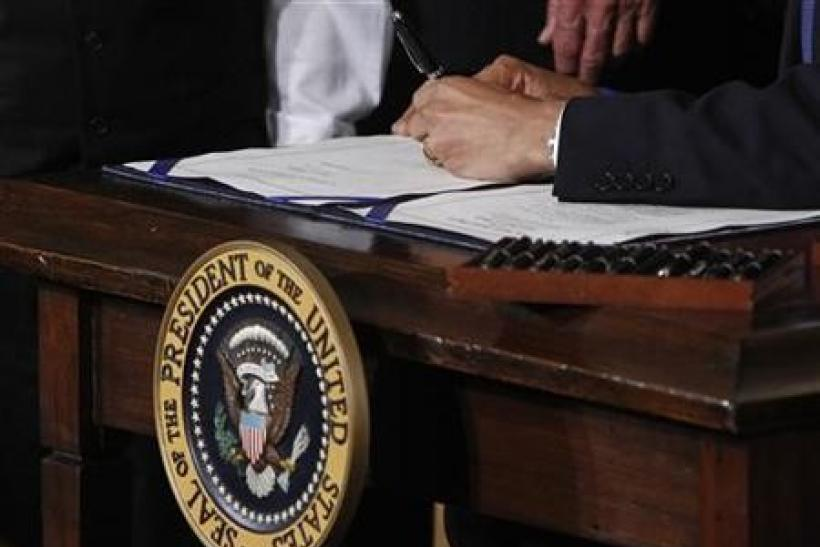 President Barack Obama signs the health insurance reform bill in the East Room at the White House in Washington