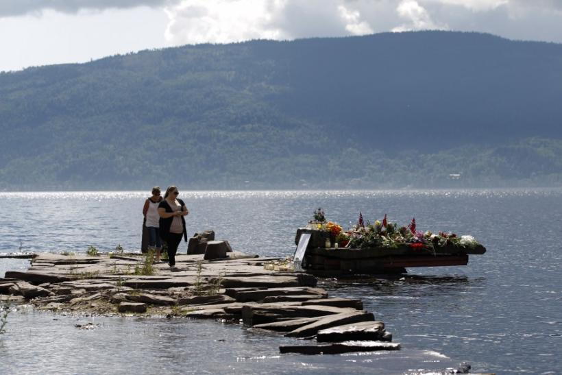 People pay their respects for victims in last Friday's killing spree and bomb attack, at temporary memorial site on shore in front of Utoeya island