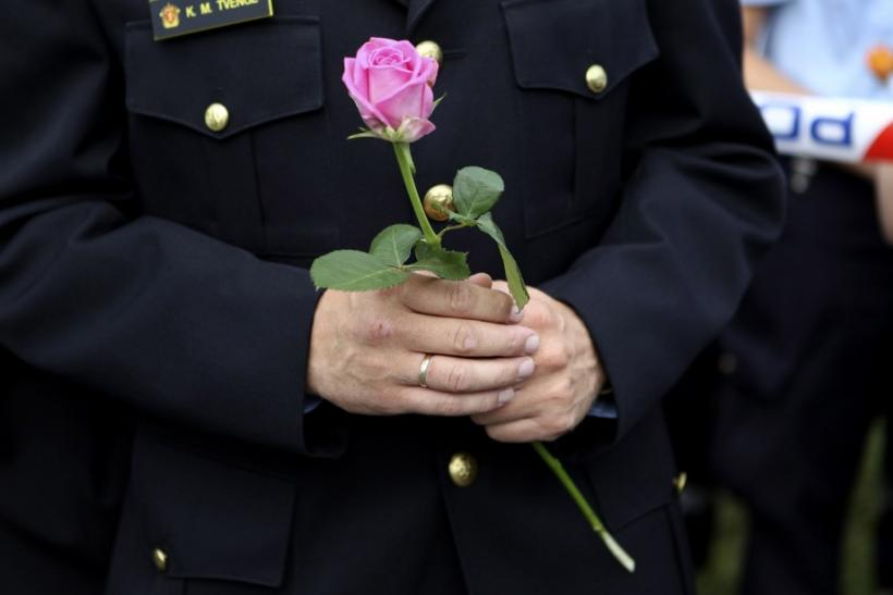 A policeman holds a flower as he takes part in a march near Utoeya island to pay their respects for the victims of the killing spree and bomb attack in Norway, in the village of Sundvollen