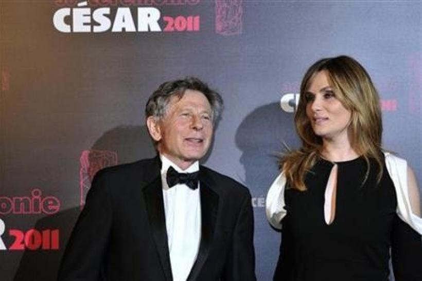 Film director Roman Polanski poses with his wife, French actress and singer Emmanuelle Seigner, as they arrive at the 36th Cesar Awards ceremony in Paris