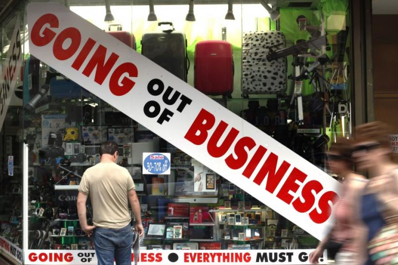 A man stands outside a store advertising that it is going out of business in New York 19/07/2011