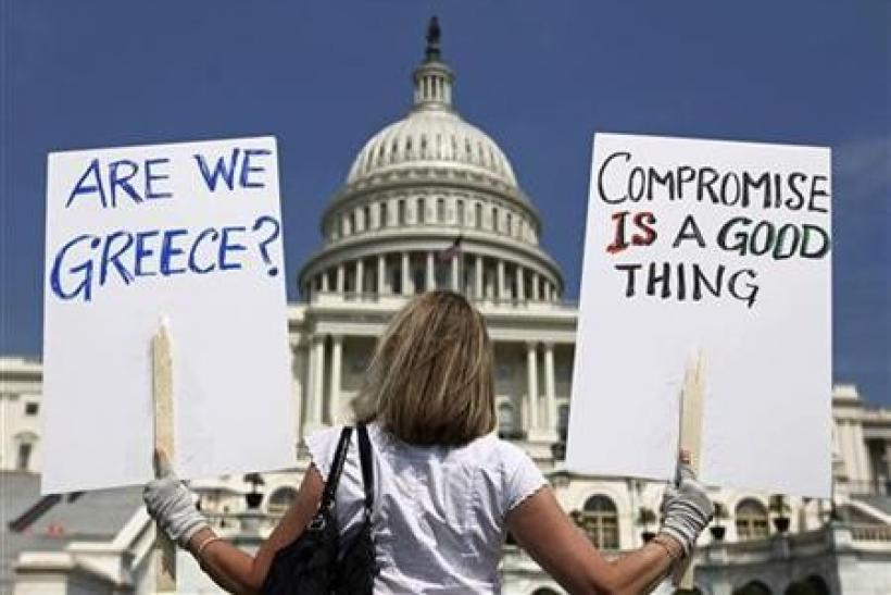 A demonstrator holds placards to protest U.S. debt in front of the Capitol