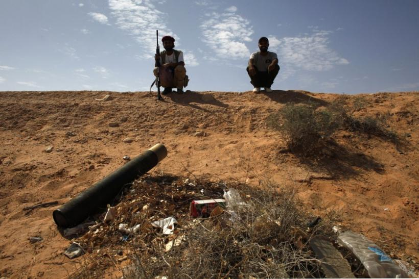 Libyan rebel fighters sit on a ridge near a tank shell after overrunning a government army position in the village of Hawamid