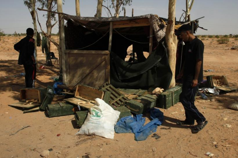 Libyan rebel fighters look at makeshift living quarters abandoned by government army soldiers after rebels overran their position in the village of Hawamid