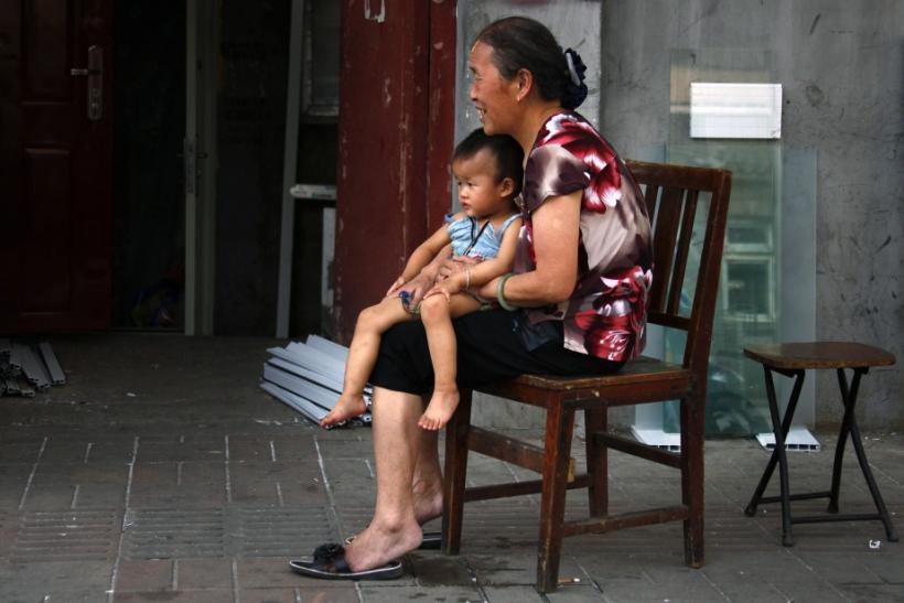 A woman sits on a chair with her grandchild along a main road in Beijing