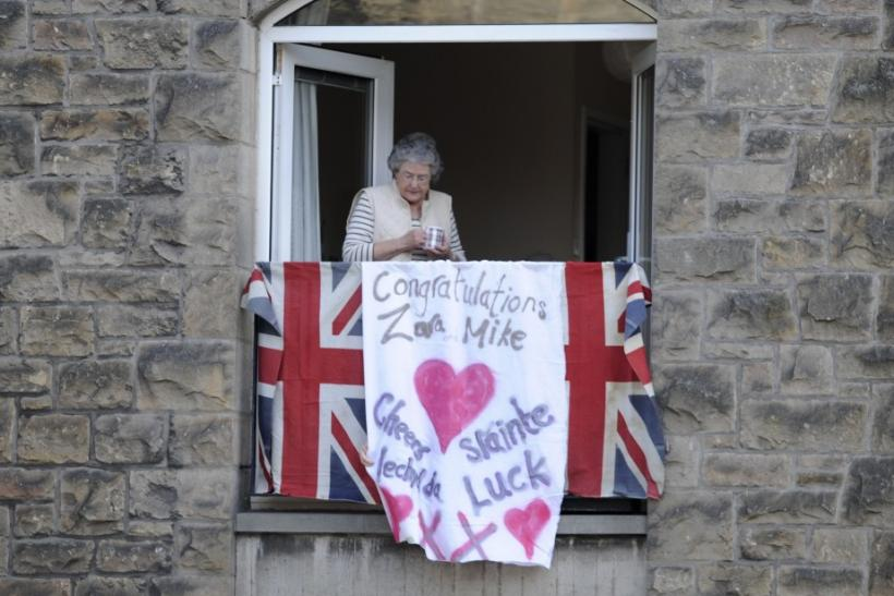 A women watches from her window before the marriage of Britain's Zara Phillips and Mike Tindall in Edinburgh