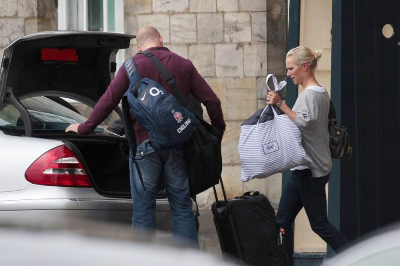 Britain's Zara Phillips, the eldest granddaughter of Queen Elizabeth, and England rugby captain Mike Tindall, carry bags to a car outside Holyrood Palace, after their marriage on Saturday, in Edinburgh, Scotland