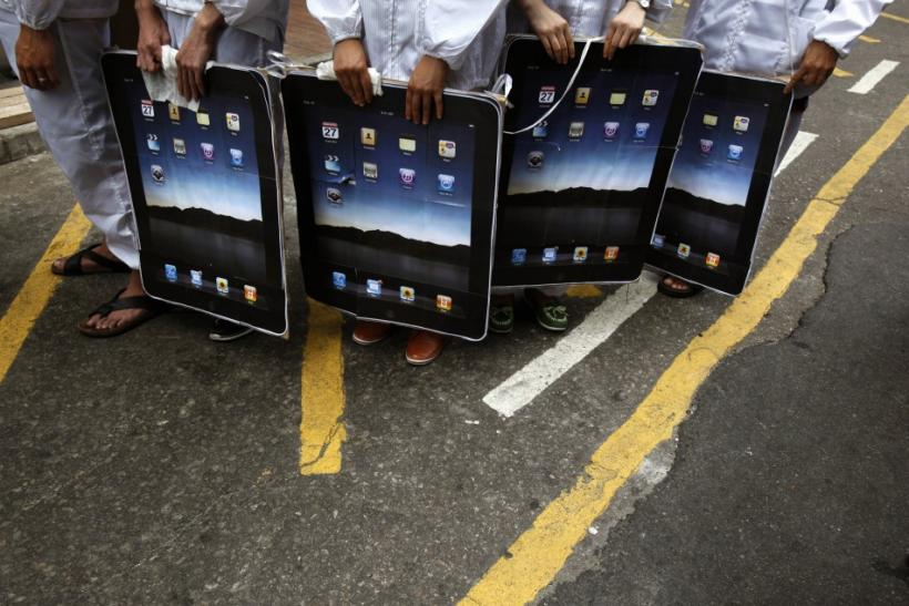Protesters carry paper cutouts of Apple iPads during a street drama in Hong Kong