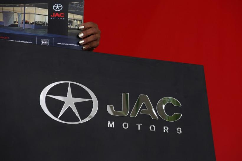 Vendor arranges publicity material of China's JAC Motors at a dealership in Sao Paulo