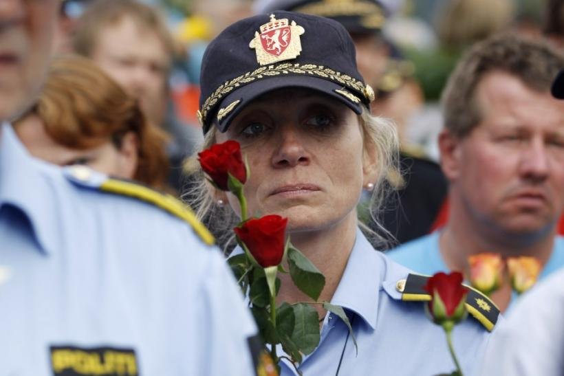 A police woman holds flowers as she takes part in a march near Utoeya island to pay their respects for the victims of the killing spree and bomb attack in Norway, in the village of Sundvollen