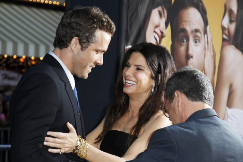 """Sandra Bullock (R) greets cast member Ryan Reynolds (L) at the world premiere of the film """"The Change-Up"""" in Los Angeles"""