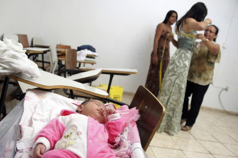 A child sleeps in a makeshift cot as inmates of the Women's Prison of Brasilia prepare for the third annual beauty pageant titled Miss Penitentiary, in Brasilia
