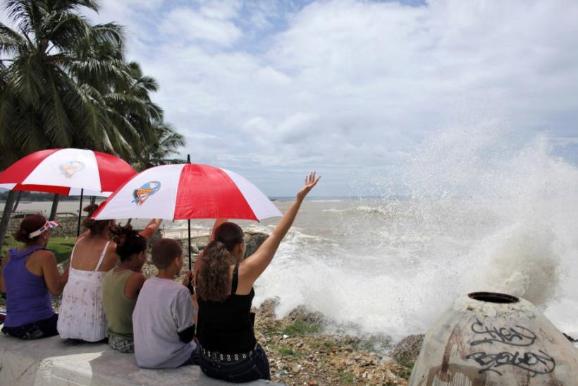 Residents sit at the malecon as Tropical Storm Emily arrives to Santo Domingo