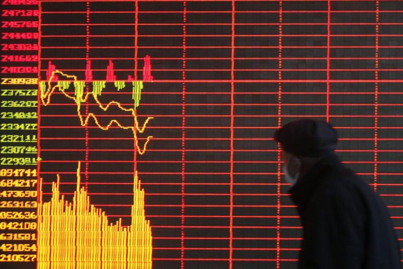 An investor looks at a screen showing stock information at a brokerage house in Taiyuan
