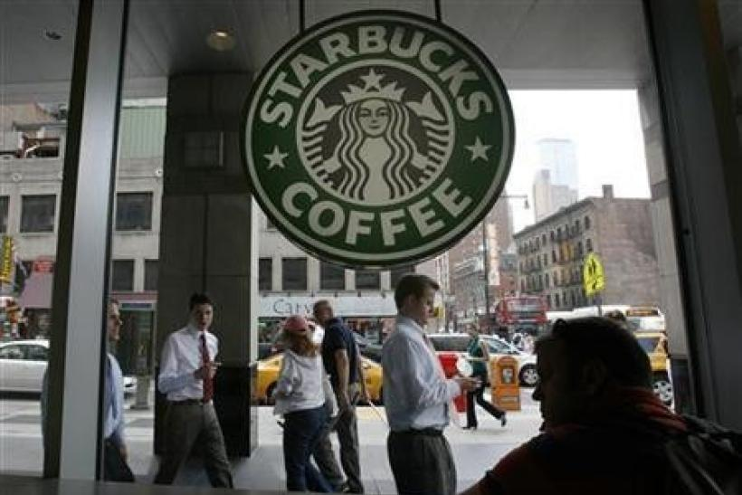 Poeple walk past a Starbucks outlet in New York