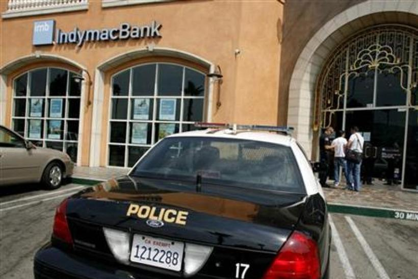 A customer talks to a police officer at a closed branch of IndyMac Bank in Burbank