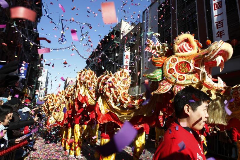 Confetti falls as a dragon dance troupe performs during the annual lunar new year parade in New York's Chinatown
