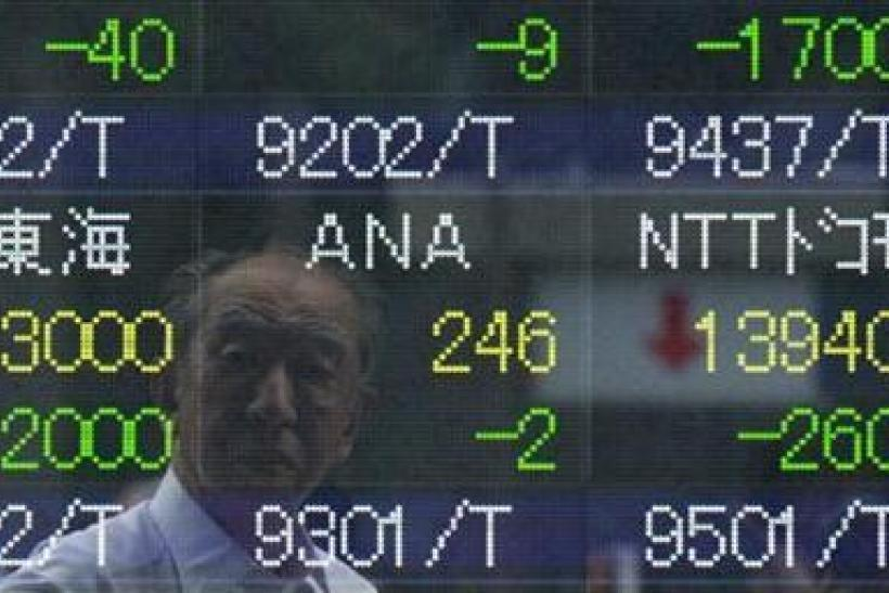 A man is reflected on an electronic stock quotation oard outside a brokerage in Tokyo August 5, 2011.