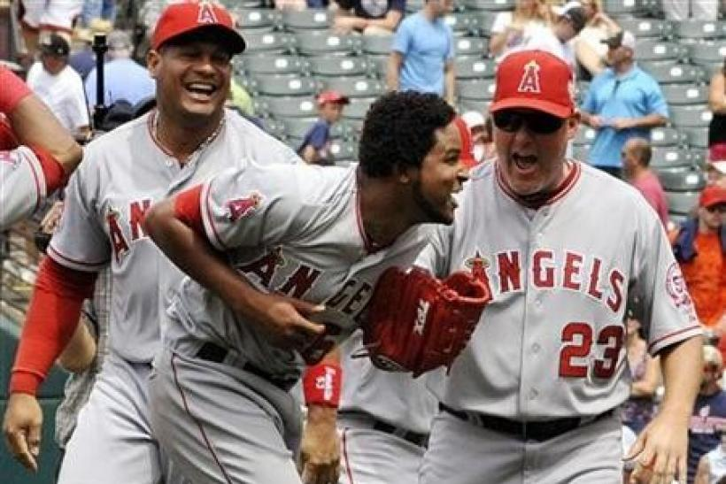 Los Angeles Angels' pitcher Ervin Santana (C) celebrates with pitching coach Mike Butcher (23) and Bobby Abreu (L) after throwing a no hitter during the MLB American League baseball game against the Cleveland Indians in Cleveland, Ohio
