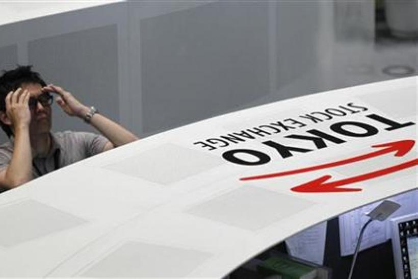 An employee of the Tokyo Stock Exchange reacts as he watches a stock index board in Tokyo