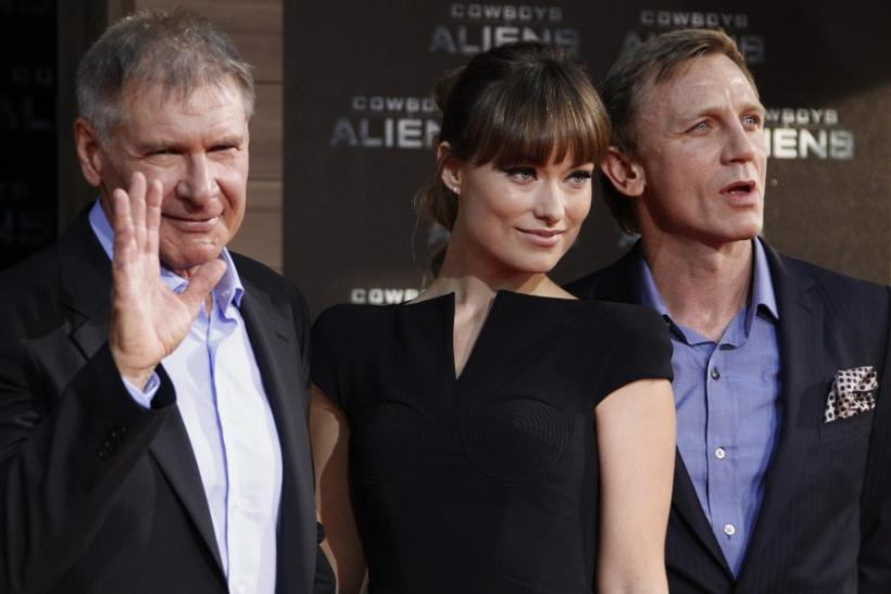 Cast members Harrison Ford, Olivia Wilde and Daniel Craig (L-R) pose for pictures as they arrive for the German premier of the movie 'Cowboys and Aliens' in Berlin
