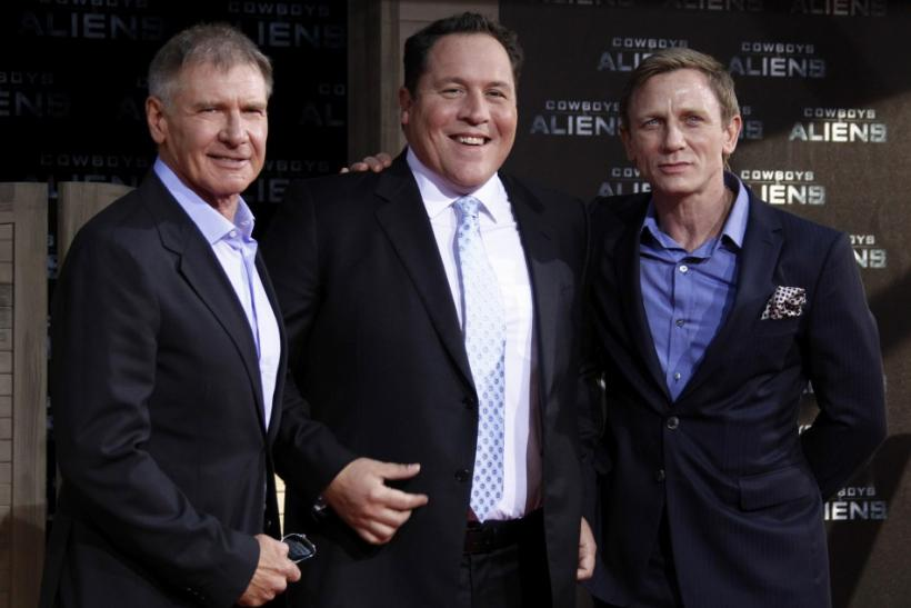 Cast members Harrison Ford (L) and Daniel Craig (R) pose with director Jon Favreau before the German premier of the movie 'Cowboys and Aliens' in Berlin