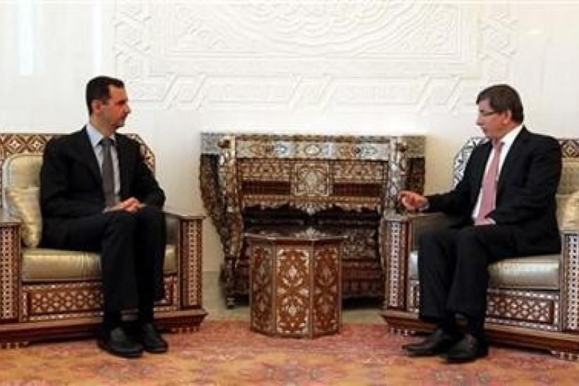 "Syria""s President Bashar al-Assad (L) meets with Turkish Foreign Minister Ahmet Davutoglu in Damascus"