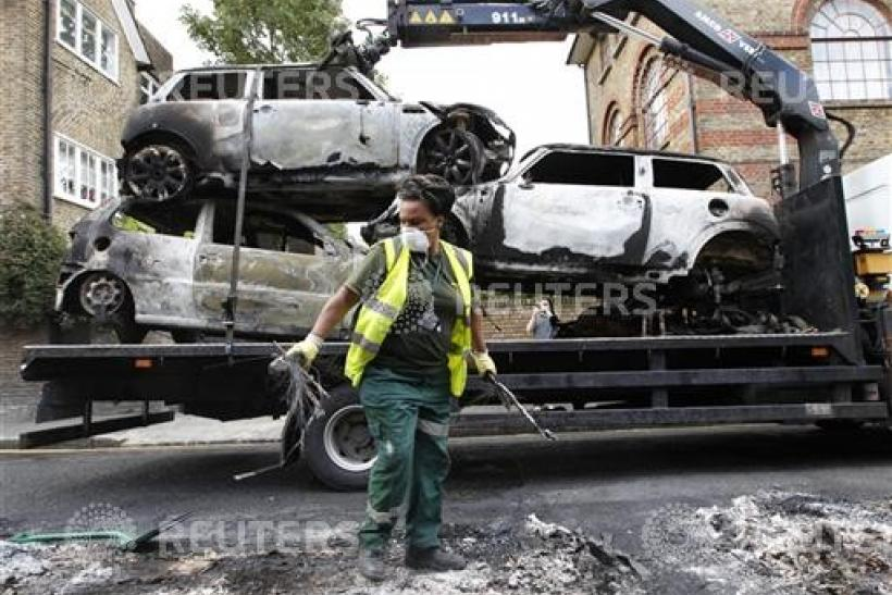 A council worker clears the remains of destroyed vehicles in Hackney, north London