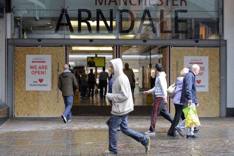 People walk past a boarded up entrance to the Arndale centre in Manchester, northern England