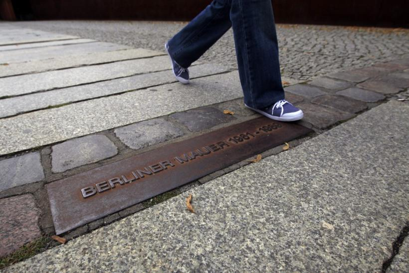 A person walks across plaque that shows where Berlin Wall used to stand at Berlin Wall memorial site in Bernauer Strasse